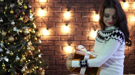 obter : Young woman with gift box on Christmas scenery background. Stock Footage