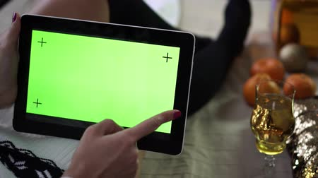 шампанское : A tablet with an empty green screen in the hands of a woman. Christmas and New year.