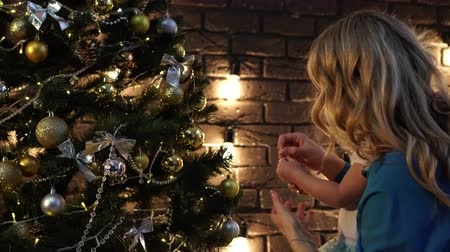 garlands : Happy family, mom and daughter decorate the Christmas tree.