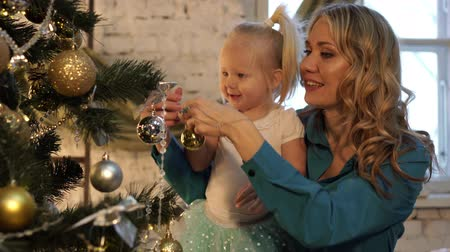garlands : A woman with a child decorate the Christmas tree.