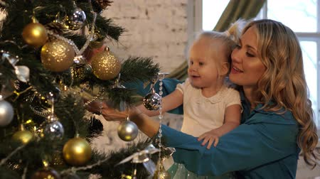 garlands : Happy family, mother and daughter decorate the Christmas tree. New year and Christmas. Stock Footage