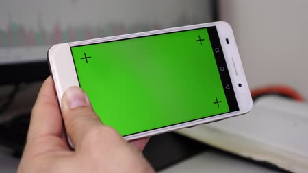 érintőképernyő : A man holds a smartphone with a green screen and touches the display with his finger.