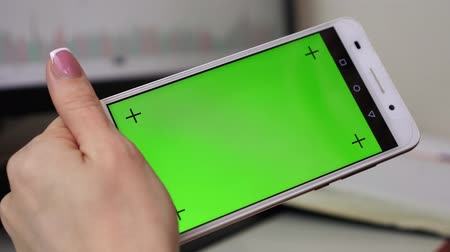 érintőképernyő : A woman holding a smartphone with a green screen and touches the display with her finger.