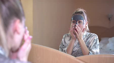 glinka : woman in front of the mirror causes a cosmetic mask for the face