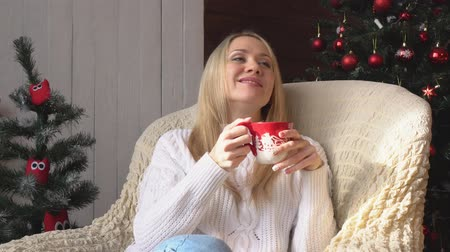 kufel : A woman in a chair drinking coffee or tea on a Christmas tree background.