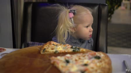 голодный : Little baby girl eating pizza in cafe. Стоковые видеозаписи