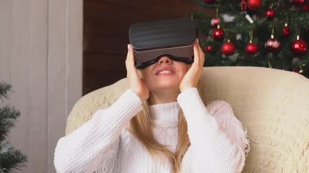 mounted : Woman in virtual reality glasses on Christmas tree background. Stock Footage