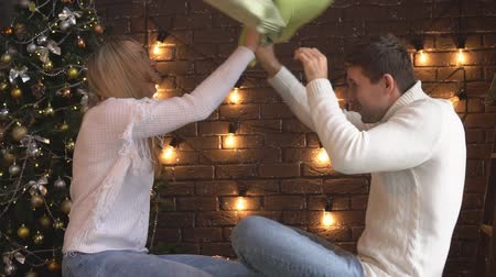 szenteste : Young couple fighting with pillows on Christmas tree background.