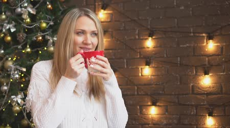 noel ağacı : Christmas, a young woman in a white sweater drinking coffee or tea from a mug. Stok Video