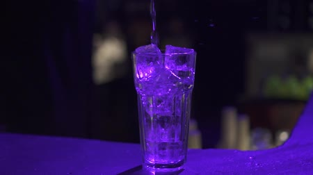 barman : liquid is poured into a glass with ice. The bartender makes a cocktail.