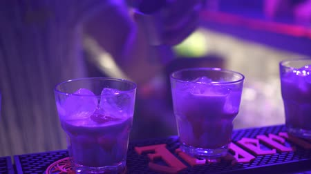 barman : A bartender at a night club makes the cocktail with ice.