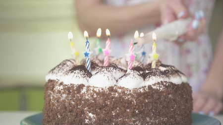 сжигание : Woman lights candles on a birthday cake, slow motion.