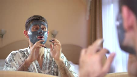 A man in front of a mirror on the face of a cosmetic clay mask.