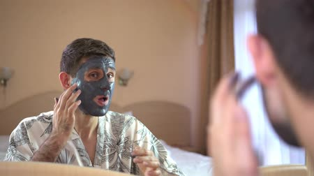 A man uses a face mask cream. Mens beauty, skin care.