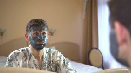 A surprised man uses a cream or face mask.