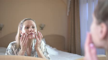 продукты : A young woman in front of a mirror applies a cream or a cosmetic clay mask on her face.