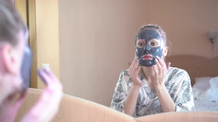 Facial skin care. A woman at home puts a comet mask on her face. Stock Footage