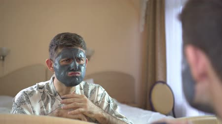 glinka : Thoughtful man uses a cream cosmetic face mask. Skin care. Wideo