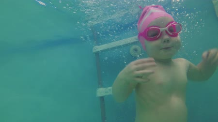 A small child learns to swim in the pool, slow motion.