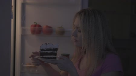 Woman at night pulls out a cake from the fridge