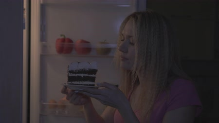 Woman at night wants to eat a piece of cake, diet, sweet tooth.