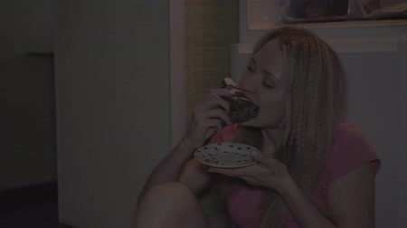 Woman enjoying eating cake at night in the kitchen.