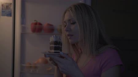 A woman wants to eat a piece of cake at night, diet, sweet tooth. Stock Footage
