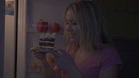 Night, kitchen, woman pulls a piece of cake out of the fridge.
