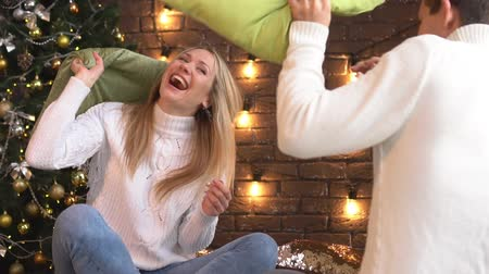 szenteste : A young couple fights with pillows at Christmas.