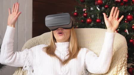 szenteste : Young blonde woman wearing virtual reality glasses. Christmas, slow motion. Stock mozgókép