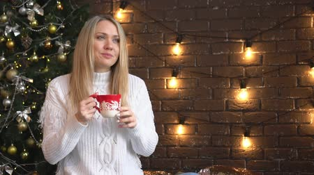 Christmas, a beautiful woman in a white sweater drinking from a mug.