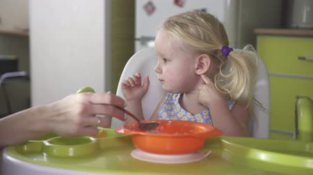 Mom feeds a spoon a small child. Stock Footage