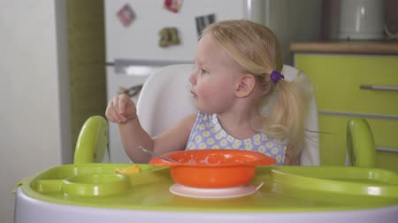 happy little girl eats with a spoon while sitting at table.