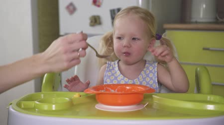 Mom feeds her little daughter porridge with a spoon.