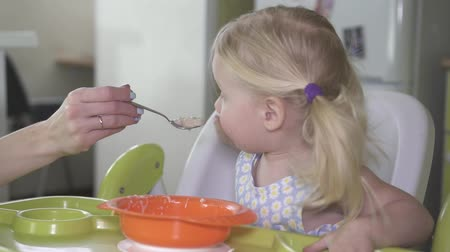 níveis : A little baby girl does not want to eat porridge and is naughty. Stock Footage