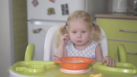 Little sad girl is sitting at the table with a plate of porridge.