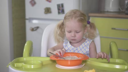 níveis : Little baby girl does not want to eat porridge.