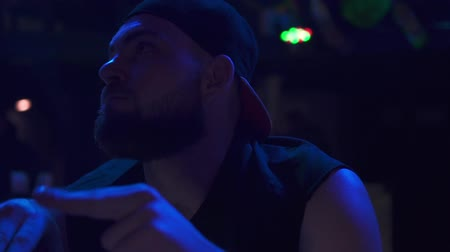 A man resting in a nightclub and listening to music. Stock Footage