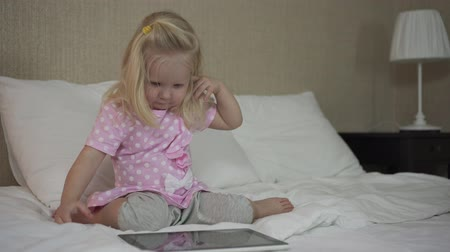 Little baby girl with tablet on bed.