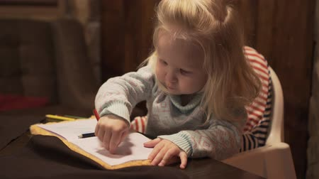 crayon : Little girl baby blonde draws with pencil.