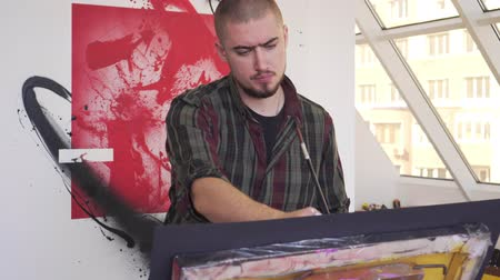 vászon : Modern artist man draws a picture in an art studio.