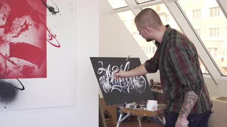 vászon : A young modern artist paints a picture in an art workshop.