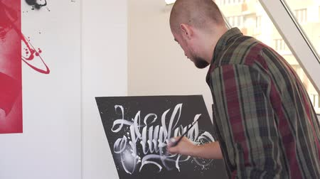 płótno : A contemporary artist paints a picture in an art workshop. Calligraffiti style.