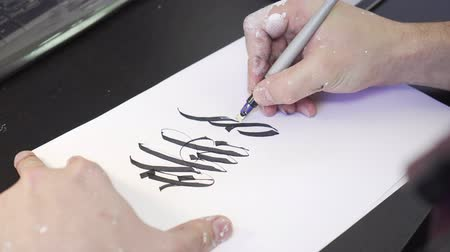 warsztat : artist makes a sketch on a sheet of paper. Painting, calligraffiti. Wideo