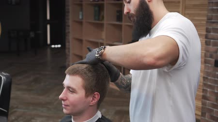 A barber male with a beard cuts a client in a barbershop. 動画素材