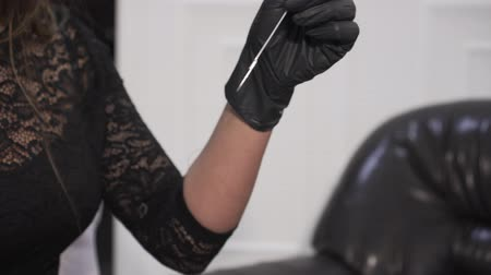 A female tattoo artist pulls out a disposable tattoo needle.