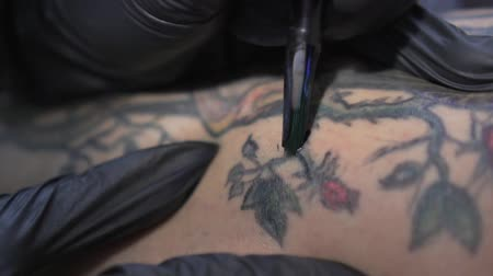 Woman make a tattoo in the form of drawing flowers. Stock Footage