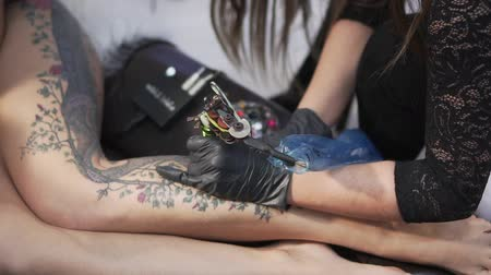 guns : Woman tattoo master makes a tattoo to a woman. Stock Footage