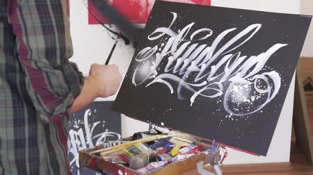 талант : A man artist draws a picture on the easel.