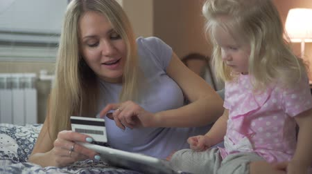 cartão de crédito : Happy family shopping online with a Bank card tablet.